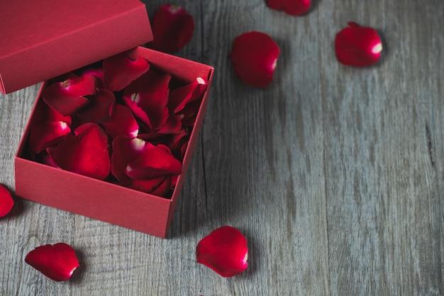 Czerwone pudełko z płatkami róż w środku, umieszczone na szarej drewnianej podłodze, widok z góry i kopia przestrzeń, motyw walentynkowy