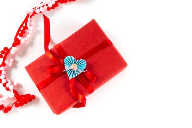 Czerwone pudełko z sercem i kokardą na białym tle. koncepcja opakowania walentynki 14 lutego. leżał z płaskim, kopia przestrzeń, widok z góry.