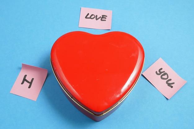 Czerwone pudełko z sercem i naklejkami o miłości