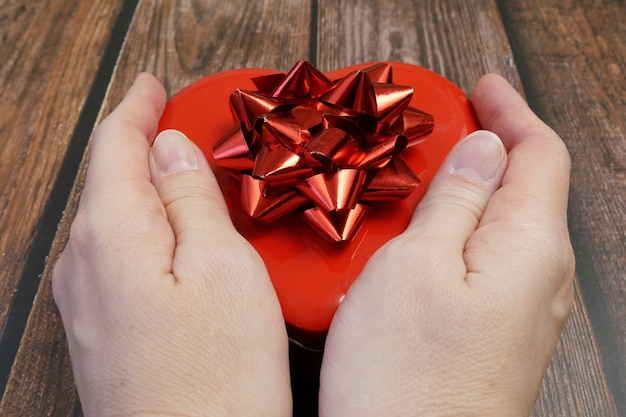 Czerwone pudełko z sercem z kokardą w rękach