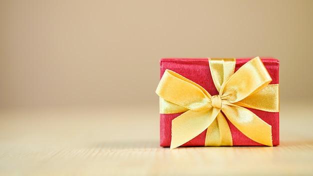 Czerwone pudełko z złote wstążki na drewnianym stole tło wesołych świąt i szczęśliwego nowego roku. wakacje i impreza
