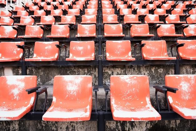 Czerwone puste i stare plastikowe siedzenia na stadionie.