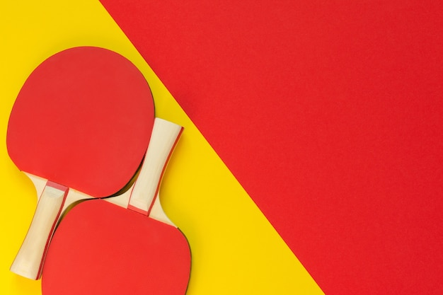Czerwone rakiety tenisowe do ping-ponga i na białym tle na czerwonym i żółtym tle, sprzęt sportowy do tenisa stołowego
