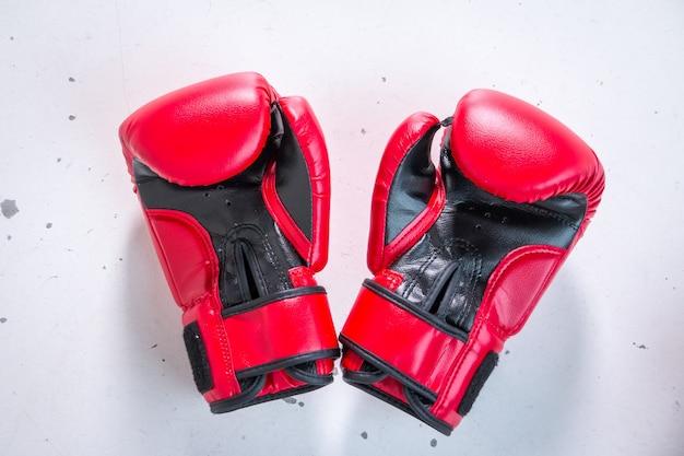 Czerwone rękawice bokserskie na białym tle na białym szarym tle. widok z góry. sekcje sportowe dla dzieci. aktywny i zdrowy tryb życia