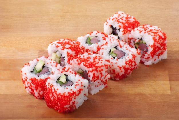 Czerwone rolki sushi kalifornijskie na drewnianym talerzu