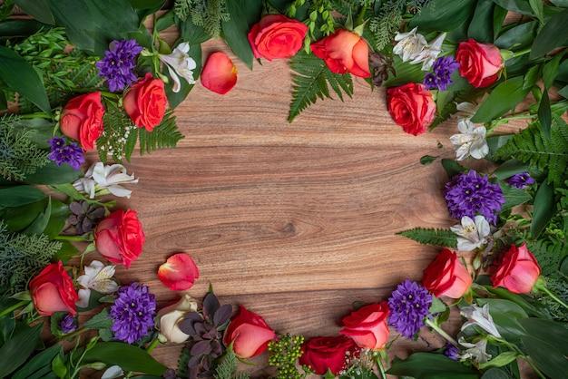 Czerwone róże, biała alstroemeria, gypsophila elegans. świąteczna dekoracja na drewnianej powierzchni.