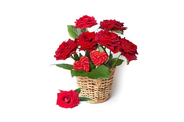 Czerwone róże i cukierki serca w wiklinowym koszu