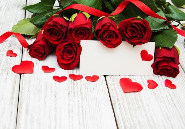 Czerwone róże i kartka z pozdrowieniami