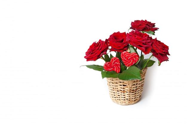 Czerwone róże i kierowi cukierki w łozinowym koszu na białym odosobnionym tle. kartka z życzeniami.