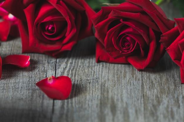 Czerwone róże i płatki na szarej drewnianej podłodze, widok z góry i miejsce, motyw walentynki