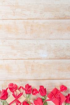 Czerwone róże i pudełka i wystrój serca na białym drewnianym stole. walentynki wakacje