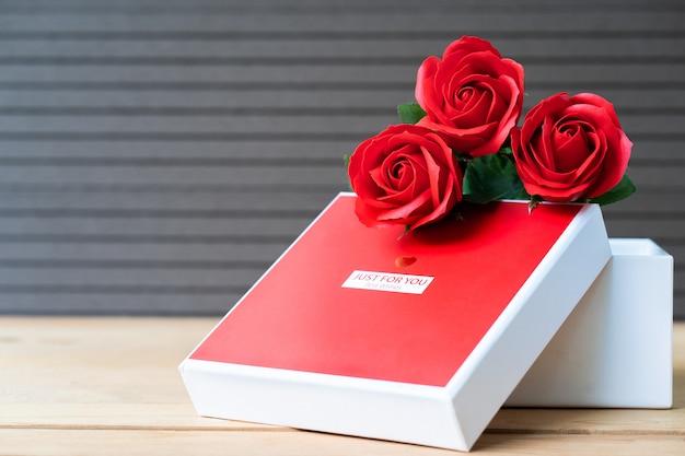 Czerwone róże i pudełko w kształcie serca na drewnie