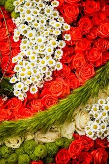 Czerwone róże i rumianki jako wzór do projektowania ślubnego