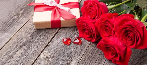 Czerwone róże kwiaty i pudełko na szarym drewnianym stole. kartka z życzeniami. skopiuj miejsce na tekst. baner poziomy - obraz