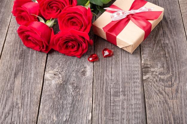 Czerwone róże kwiaty i pudełko na szarym drewnianym stole. kartka z życzeniami. skopiuj miejsce na tekst - obraz