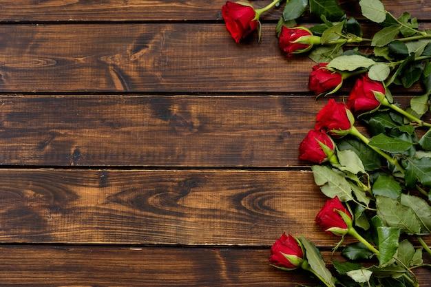 Czerwone róże na ciemnym drewnianym tle