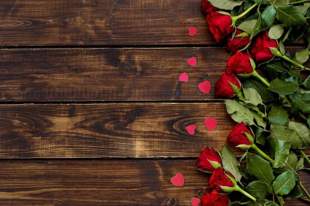 Czerwone róże na ciemnym drewnianym