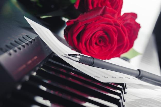 Czerwone róże na klawiszach fortepianu