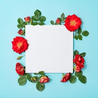 Czerwone róże na pastelowym błękicie z kartką papieru