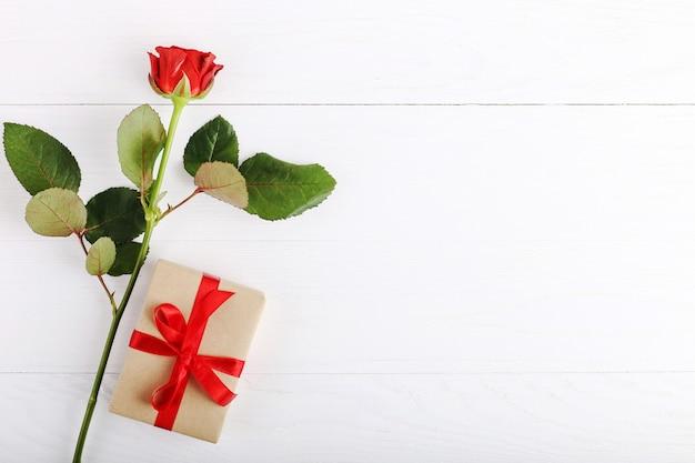 Czerwone róże, prezent na białym drewnianym stole
