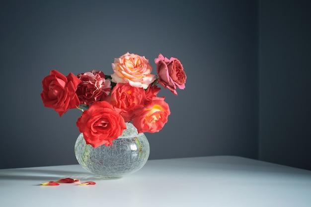 Czerwone róże w białym wazonie na szarym tle