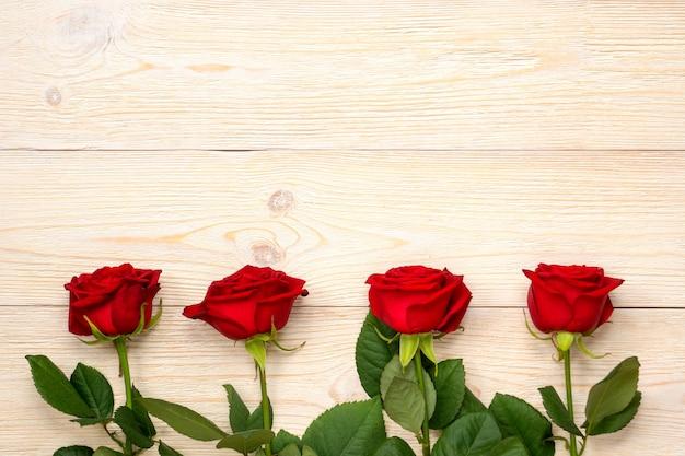 Czerwone róże w rzędzie nad białymi rustykalnymi deskami