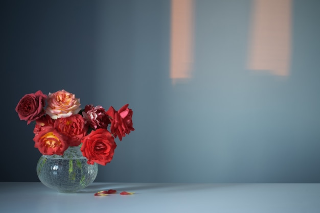 Czerwone róże w szklanym wazonie na niebieskim tle