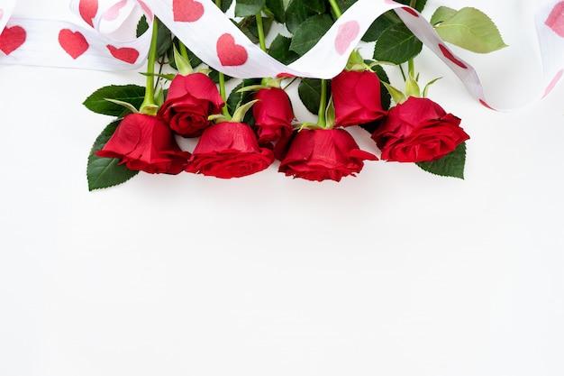 Czerwone róże z faborkiem na białym tle