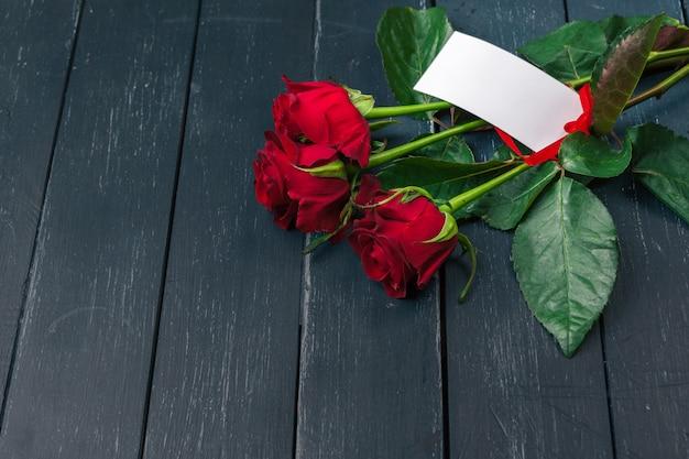 Czerwone róże z kartą wiadomości. walentynki