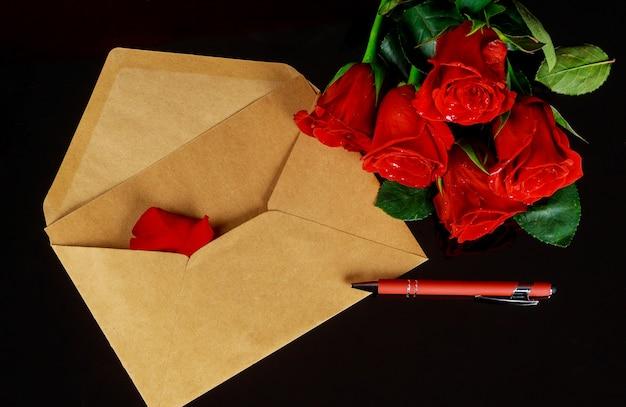 Czerwone róże z kopertą i piórem na czarnym stole. koncepcja walentynki.
