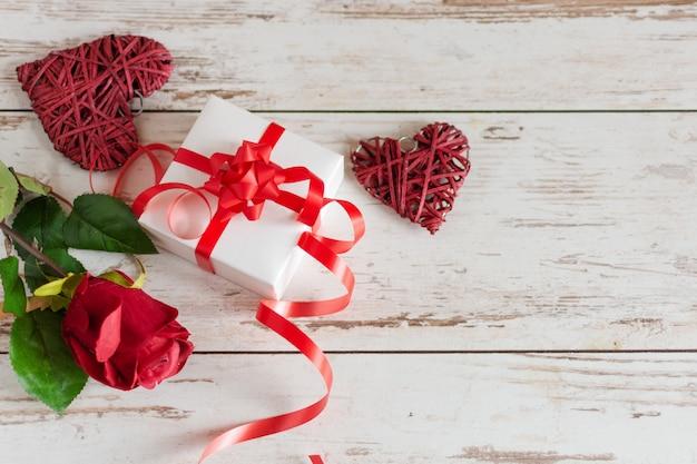 Czerwone róże z sercami i prezentem na drewnianym