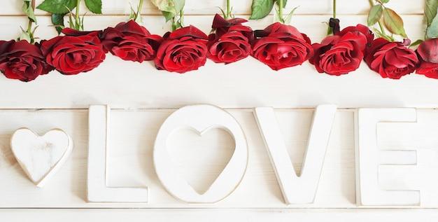 Czerwone róże z sercem, drewniane litery miłości, szablon pocztówki