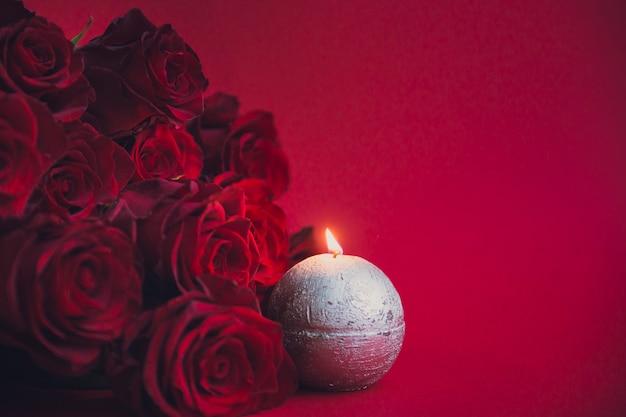 Czerwone róże z świeczką na czerwonym tle