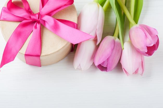 Czerwone różowe żółte tulipany i pudełko z czerwoną wstążką