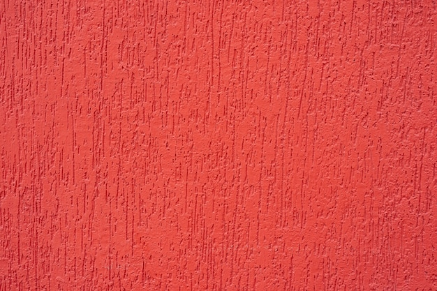 Czerwone ściany, tekstury i tła. piękna tekstura czerwonego pędzla namalowana na cementowej ścianie