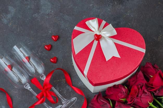 Czerwone serca, czerwone róże, dwie szklanki, pudełko w kształcie serca