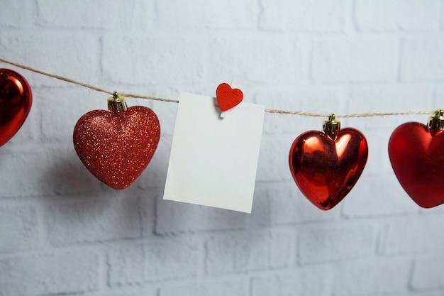 Czerwone serca i biała karta wiszą na nitce na tle cegły