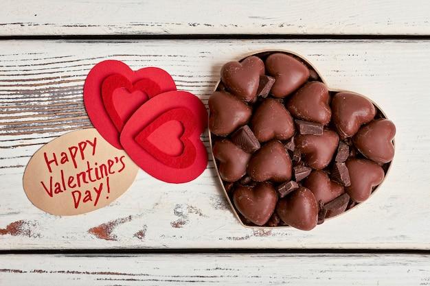 Czerwone serca i czekoladki. papier powitalny z wyjątkiem cukierków. proste słodkie powitanie.