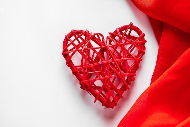 Czerwone serca i jedwabną wstążką na białym tle.