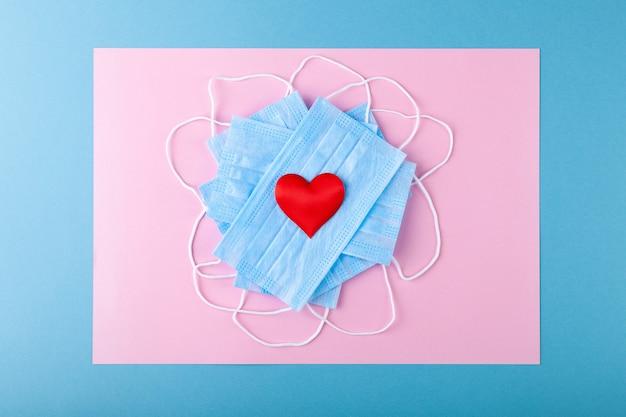 Czerwone serca i niebieska medyczna maska ochronna przeciw epidemii
