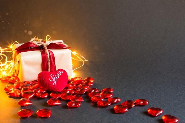 Czerwone serca i pudełko na czarnym stole