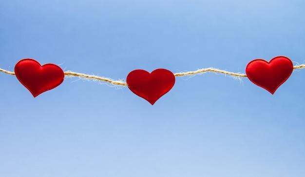 Czerwone serca jasnoniebieskie tło.