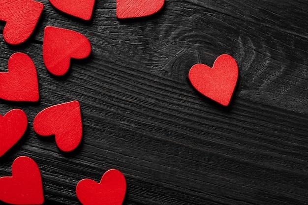 Czerwone serca na czarnym tle drewna.