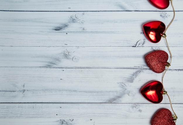 Czerwone serca na jasnym tle drewniane. walentynki