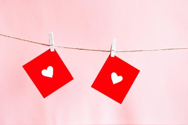 Czerwone serca ustawione na sznurku na różowej ścianie. koncepcja walentynkowa. s.