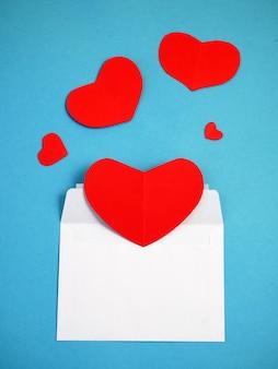 Czerwone serca w otwartej kopercie pocztowej
