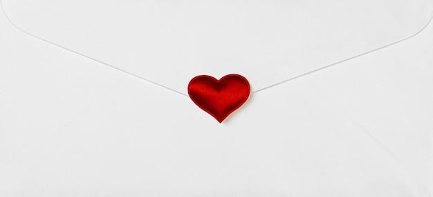 Czerwone serca wybite na białą kopertę. - koncepcja wiadomości miłości i troski.