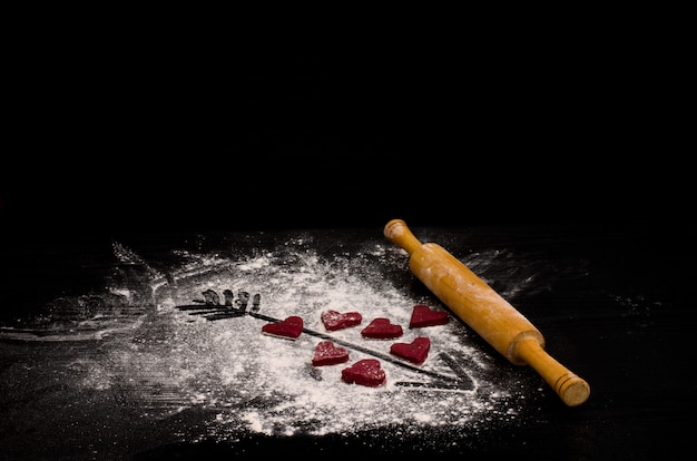 Czerwone serca z ciasta, drewniany wałek do ciasta i strzała namalowana na mące.