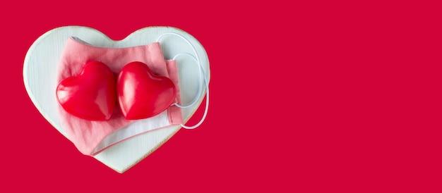 Czerwone serca z ochronną różową maską na drewnianym sercu na czerwonym tle. walentynkowa opieka koncepcyjna.