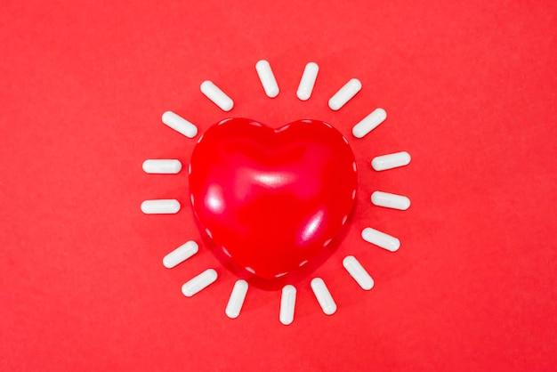 Czerwone serce i białe kapsułki pigułki na czerwono